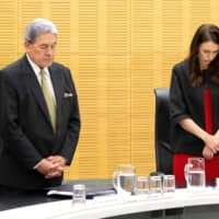 New Zealand Prime Minister Jacinda Ardern and Deputy Prime Minister Winston Peters stand with cabinet ministers as they observe a minute's silence in respect for victims of the Dec. 9 White Island volcanic eruption, at Parliament in Wellington on Monday. | AFP-JIJI