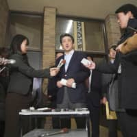 Prime Minister Shinzo Abe talks to reporters after having a phone conversation with U.S. President Donald Trump Saturday at the prime minister's official residence in Tokyo. | KYODO