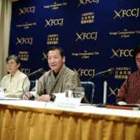 Sonam Dhendup (center) of the Parent's Committee of the Learn and Earn Program, speaks at a February news conference at the Foreign Correspondents' Club of Japan in Tokyo, while fellow member Nagwang Tobgay (right) and Yumiko Kan of Nature and Humans Japan look on. | RYUSEI TAKAHASHI