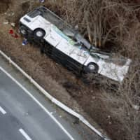 A tour bus is shown after veering off a road in Karuizawa, Nagano Prefecture, killing 13 passengers and two drivers, in January 2016. | KYODO