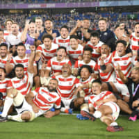 Japan's players pose after defeating Scotland in a Rugby World Cup Pool A match in Yokohama on Oct. 13. | KYODO