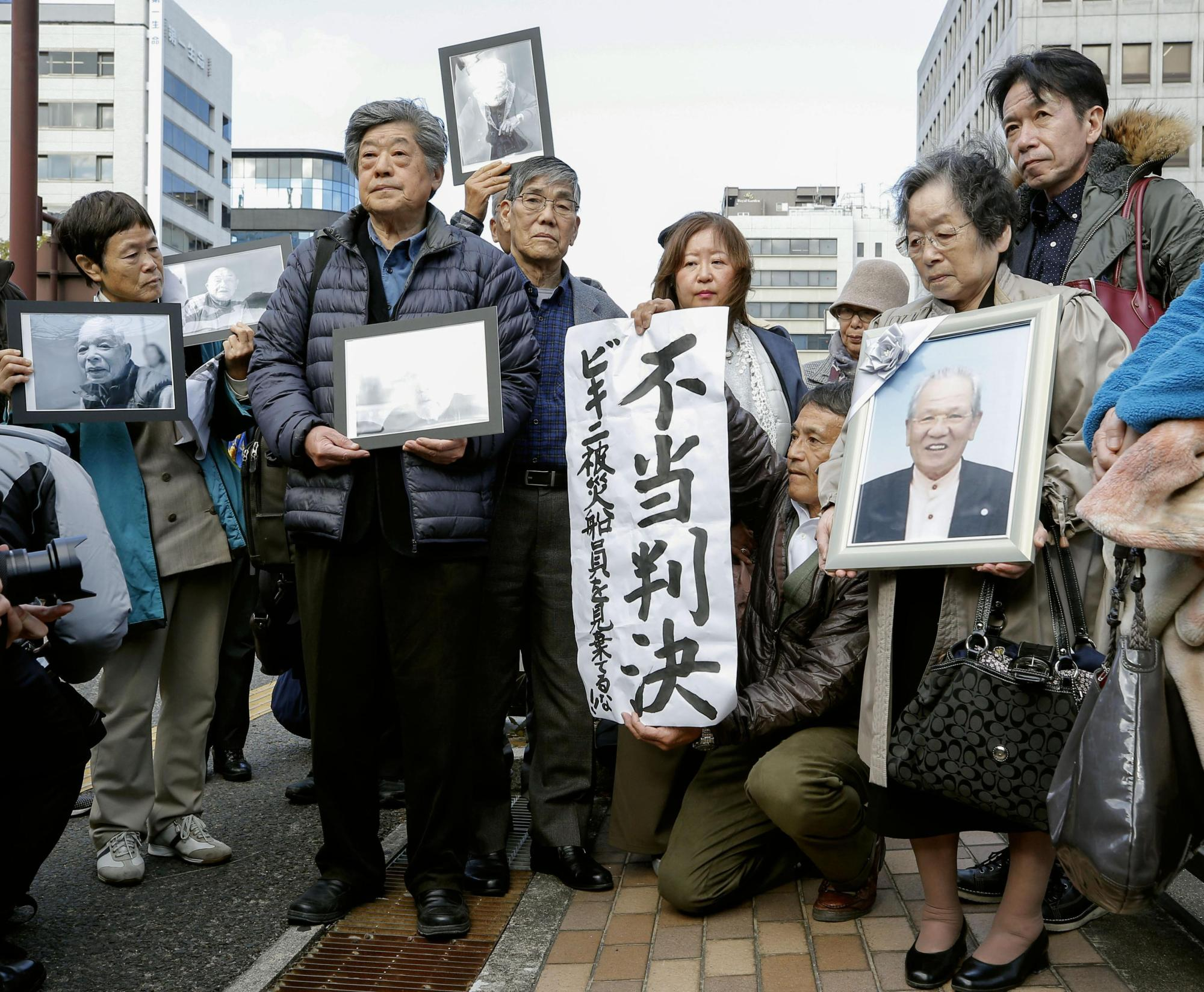 Supporters of the plaintiffs denounce a high court decision to uphold a lower court ruling that rejected a claim by former tuna fishermen and bereaved relatives for state compensation over the 1954 U.S. hydrogen bomb tests at Bikini Atoll, in Takamatsu, Kagawa Prefecture, on Thursday. | KYODO