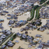 Torrential rains flood the residential areas of the Mabicho district in Kurashiki, Okayama Prefecture, in July last year. | KYODO