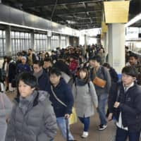 Japanese heading home for New Year's holidays crowd trains and airports