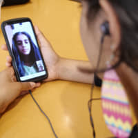 Sri Lankan national Dakshini Siriwardena, 21, talks on Skype with her younger sister, Pamalya, who left Japan after her father's business failure, on June 6. | CHISATO TANAKA