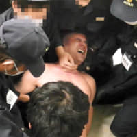 Footage showing a Kurdish man being restrained at an immigration center in Ibaraki Prefecture in January. The clip has been submitted to the Tokyo District Court. | COURTESY OF THE PLAINTIFF'S LAWYER / VIA KYODO