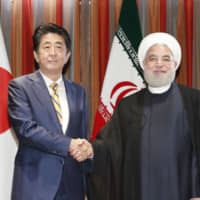 Prime Minister Shinzo Abe and Iranian President Hassan Rouhani shake hands ahead of talks in New York in September. | KYODO