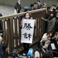 Shiori Ito holds up a sign highlighting her win in a lawsuit seeking damages from Noriyuki Yamaguchi in front of the Tokyo District Court on Wednesday.  | KYODO