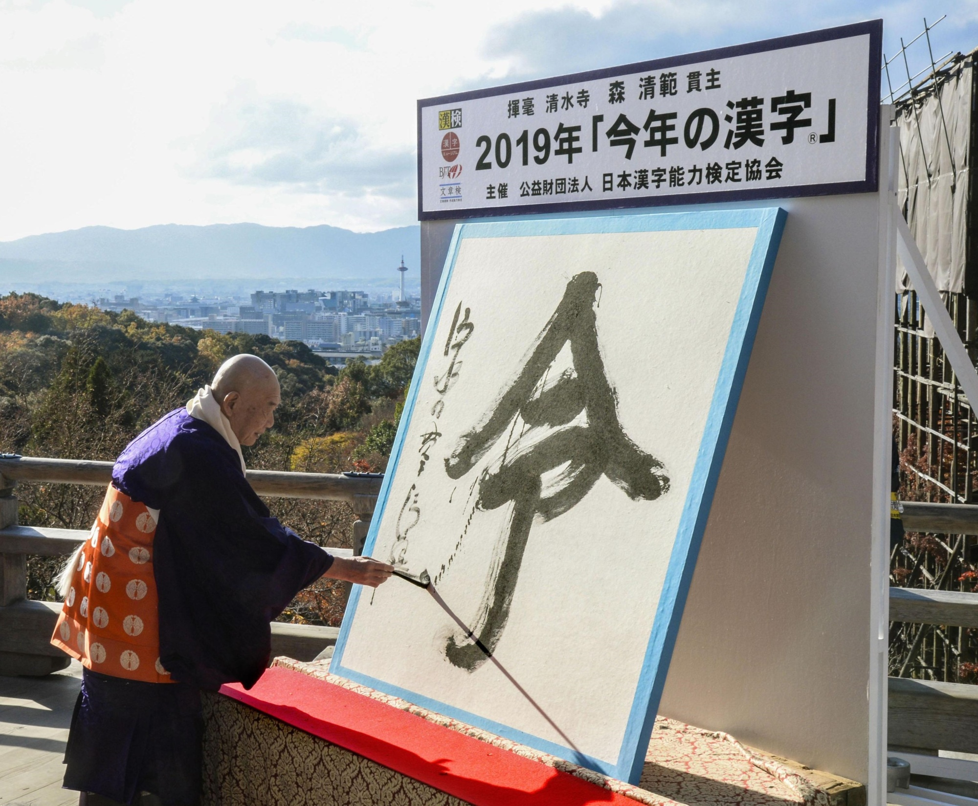 Seihan Mori, chief priest of Kiyomizu Temple in Kyoto, writes rei, the kanji character of the year, on Thursday. | KYODO