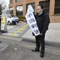 A plaintiff holds a banner that reads 'unfair ruling' outside the Nagoya District Court on Friday, after losing a case against the state over the My Number identification system. | KYODO
