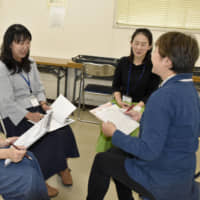 Parents share their child-rearing experiences during a meeting in October in Katano, Osaka Prefecture. | KYODO