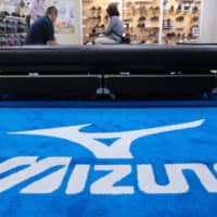 People try Mizuno Corp. shoes at the company's flagship sporting goods store in Tokyo. | BLOOMBERG