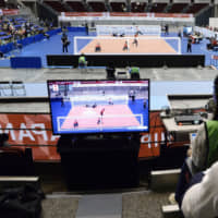Spectators don headphones so they can listen to the on-court comments of players and view the action on an arena screen. | KYODO