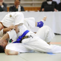 Yujiro Seto (top) competes in the men's 66-kg class judo for the visually impaired in a national competition in Tokyo in December. | KYODO