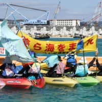 Protesters shout in canoes off Okinawa Saturday near the site of the new home for U.S. Marine Corps Air Station Futenma, a year after landfill work for the transfer began. | KYODO