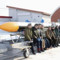 Members of Japanese startup Interstellar Technologies Inc. pose for a photo with the Momo-5 rocket last week in the town of Taiki, Hokkaido. Due to technical reasons the firm postponed Sunday's scheduled launch until at least Tuesday. | KYODO