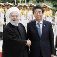 Prime Minister Shinzo Abe shakes hands with Iranian President Hassan Rouhani during a welcoming ceremony in Tehran on June 12. Abe visited Iran in hopes of brokering dialogue between Tehran and Washington. | KYODO