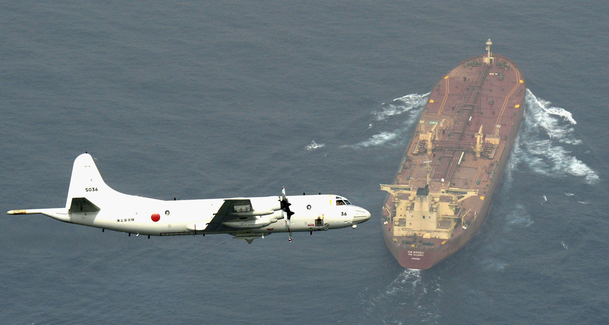 A Maritime Self-Defense Force P-3C patrol aircraft based in Djibouti is seen training over a tanker in the Gulf of Aden in August 2015. A P-3C plane is due to take part in a planned SDF mission to the Middle East. | KYODO