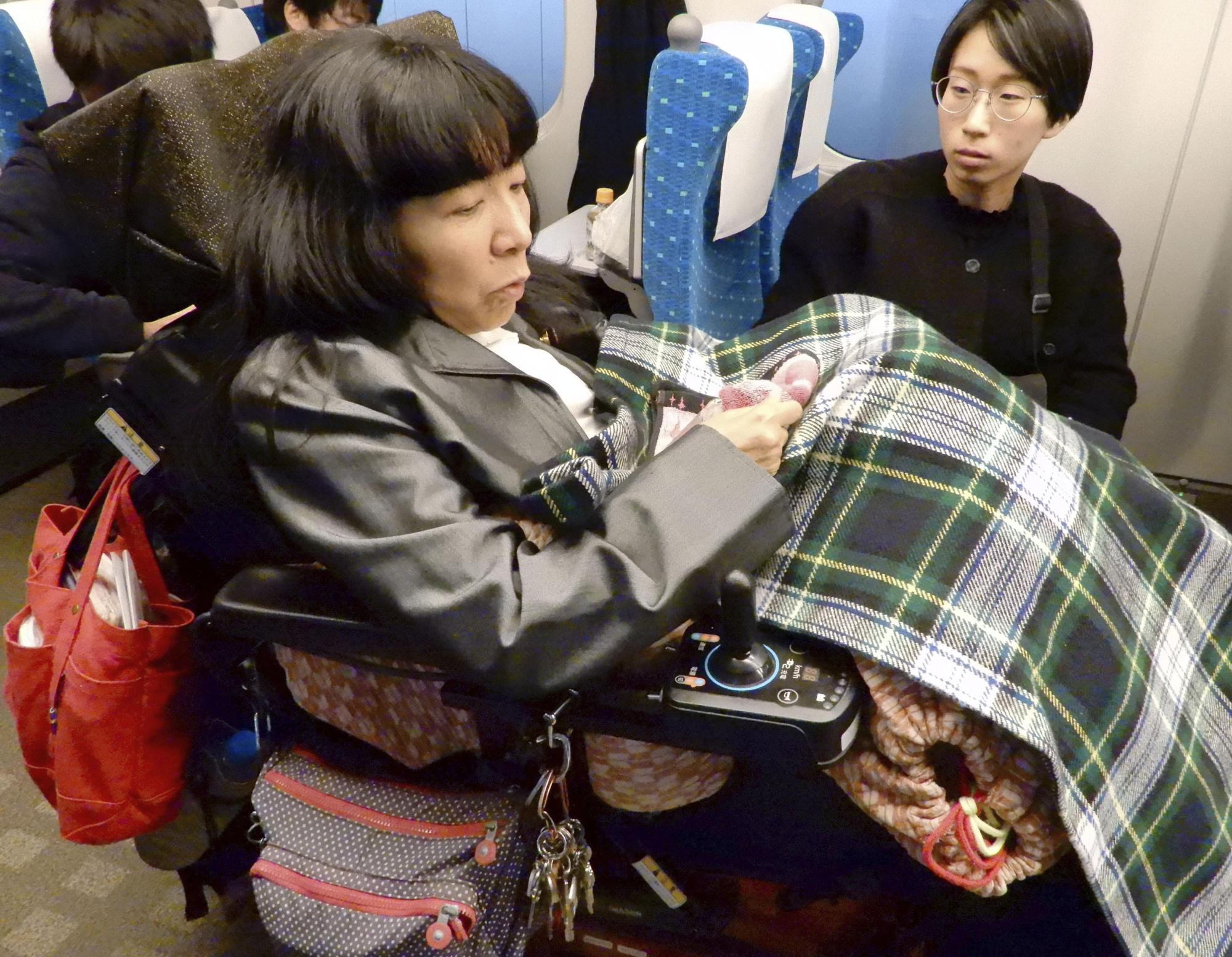 Eiko Kimura, a House of Councilors member of minor opposition party Reiwa Shinsengumi, rides a bullet train in Tokyo to survey accessibility for wheelchairs on Dec. 1. | KYODO