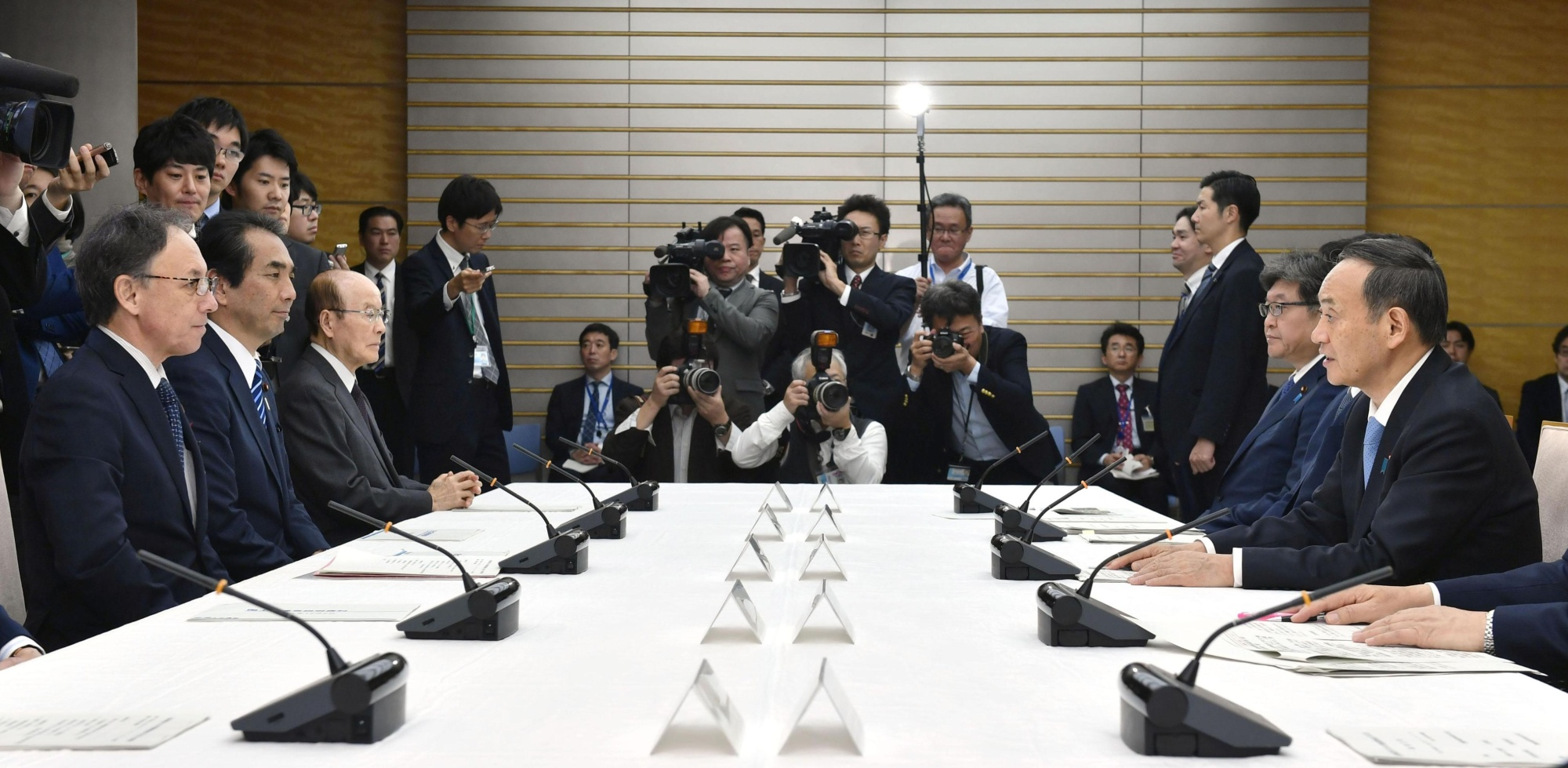 Chief Cabinet Secretary Yoshihide Suga (right) and Okinawa Gov. Denny Tamaki (left) attend a ministerial meeting on the reconstruction of Shuri Castle at the Prime Minister's Office in Tokyo on Monday. | KYODO