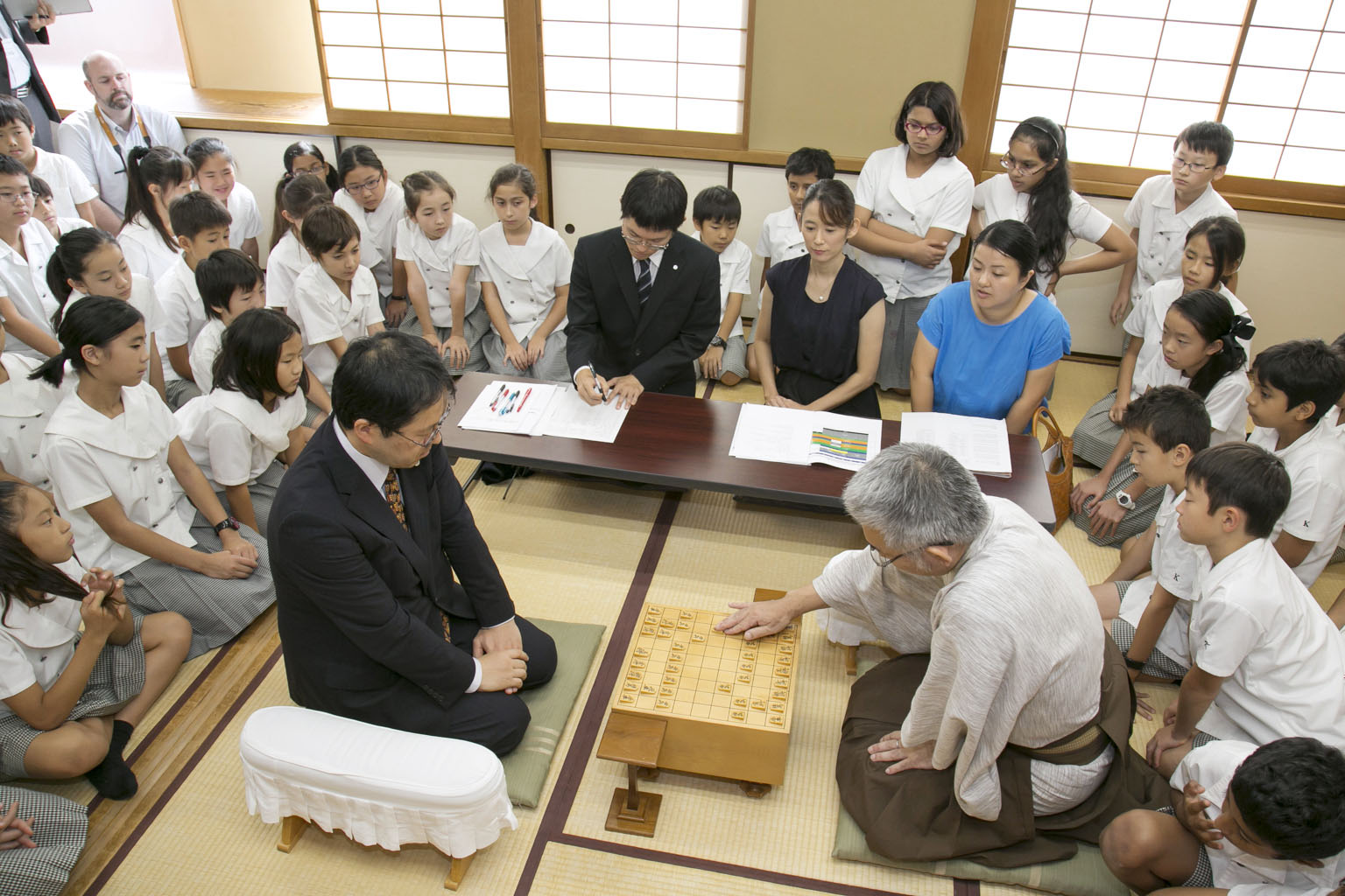 Students sitting in the formal seiza style learn shogi from professionals in Tokyo. | KYODO