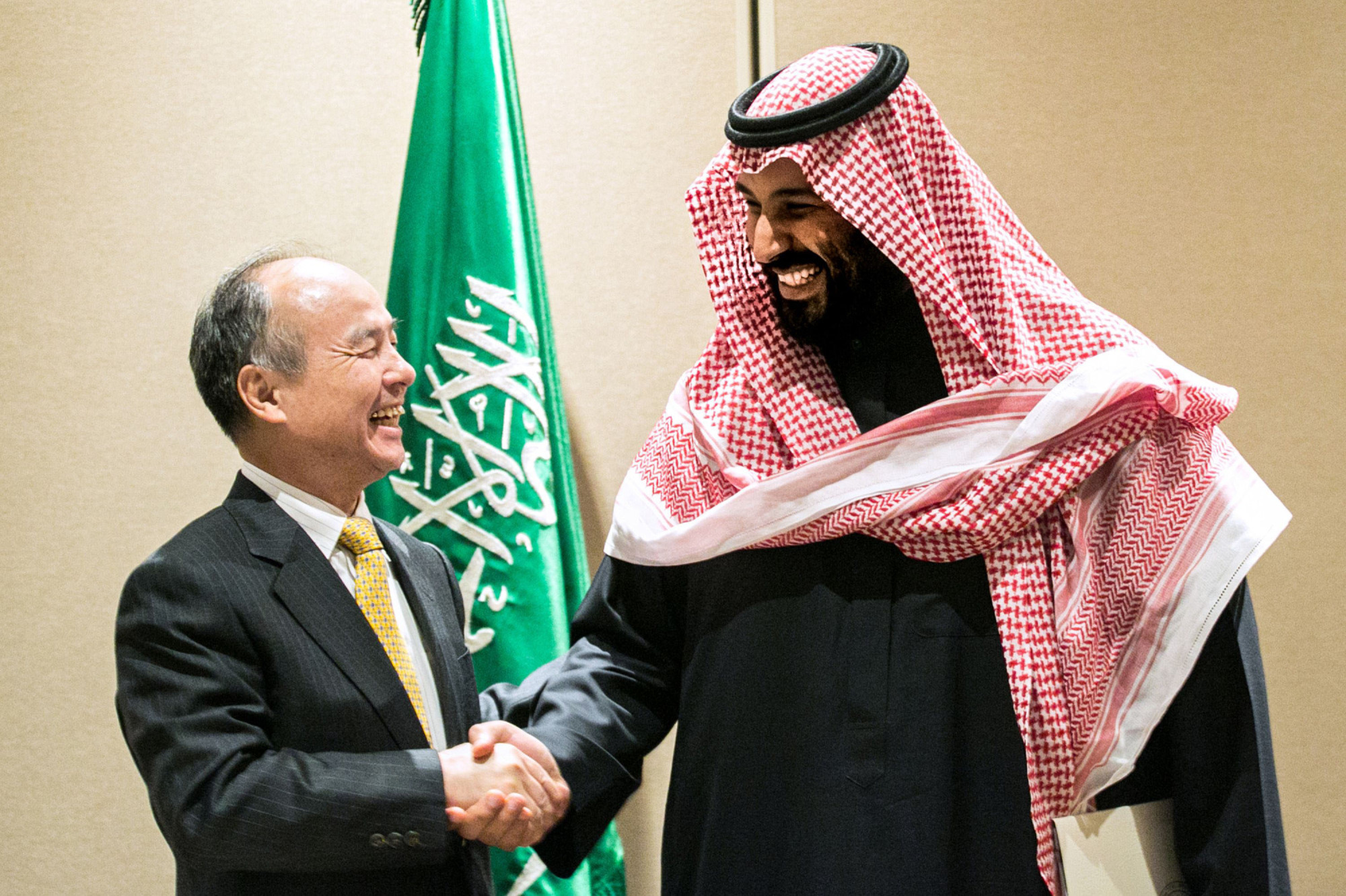 Masayoshi Son, chairman and chief executive officer of SoftBank Group Corp., and Mohammed bin Salman, Saudi Arabia's crown prince, talk after the signing of a solar energy plan in New York in March 2018. | BLOOMBERG