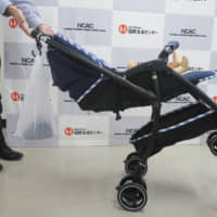 A stroller tilts backward due to the weight of a bag hung on its handle during a test at the National Consumer Affairs Center of Japan in Tokyo. | NATIONAL CONSUMER AFFAIRS CENTER OF JAPAN / VIA KYODO