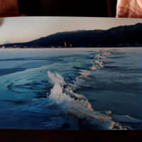 Shinto priest Kiyoshi Miyasaka displays a photo he took on Jan. 13, 2006, that shows a phenomenon called omiwatari (the crossing of the gods), which occurs when Lake Suwa freezes over and two sheets of ice collide to create a ridge across the surface. | REUTERS