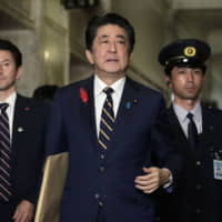Prime Minister Shinzo Abe arrives for an extraordinary session at the Lower House of the Diet in Tokyo on Oct. 4. He travels to China on Monday where he will take part in a trilateral meeting with Chinese Premier Li Keqiang and South Korean President Moon Jae-in in Chengdu on Tuesday. | BLOOMBERG