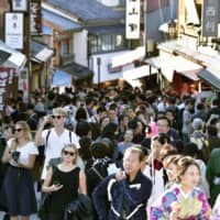 Tourists crowd a slope leading to Kiyomizu Temple, one of the most popular tourist attractions in Kyoto. | KYODO