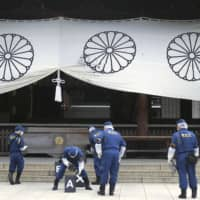 Police investigate in front of a worship hall at the war-linked Yasukuni Shrine in Tokyo on Aug. 19, after a Chinese man threw black ink on a curtain. | KYODO
