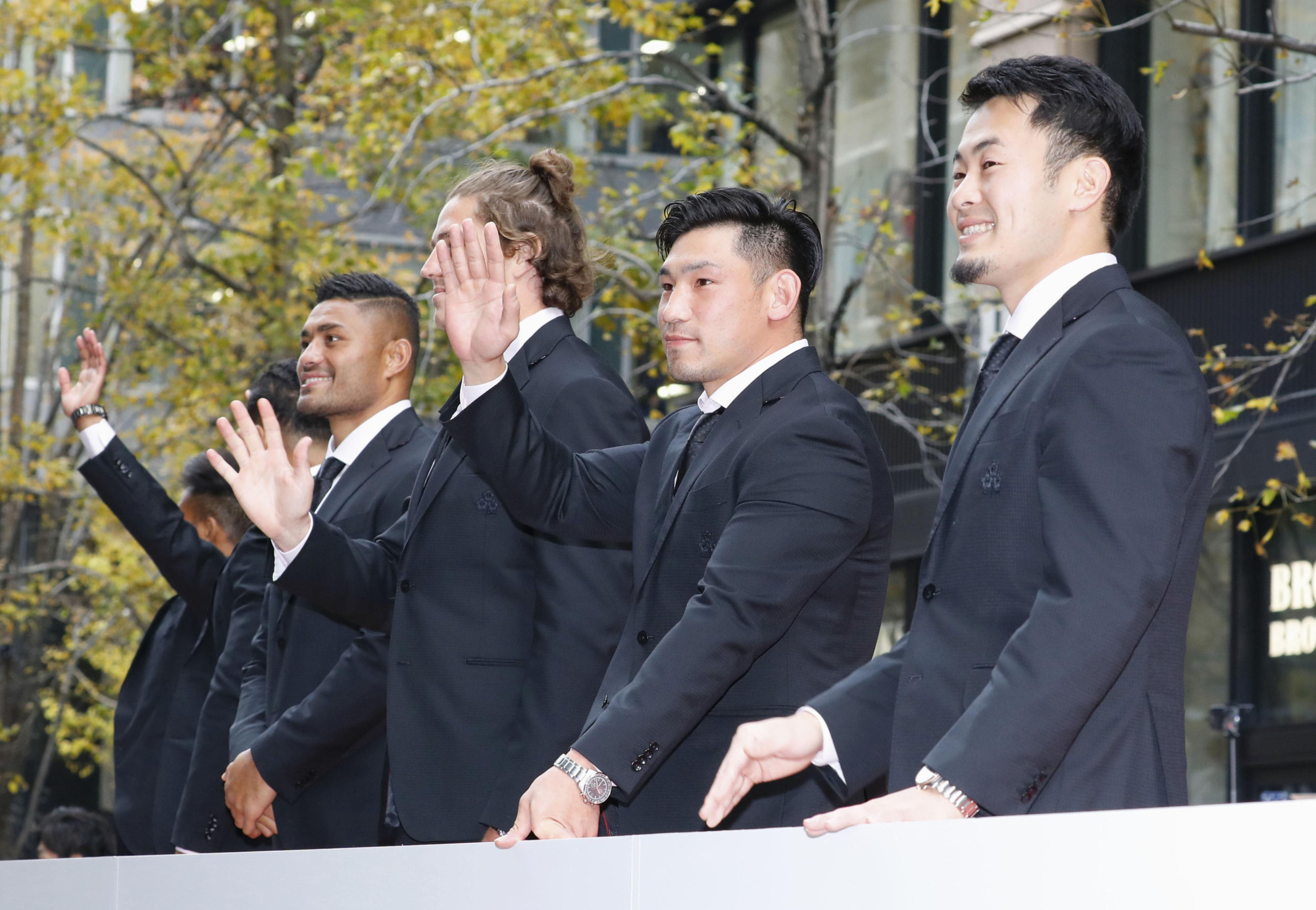 Do the wave: Members of Japan's Rugby World Cup team wave to a crowd in Tokyo's Marunouchi business district on Dec. 11. | KYODO