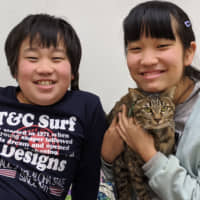 Best pals: Kentaro (left) and Yuna Shimaoka love their new cat, Latte, and Latte loves her new home. | KENJI SHIMAOKA