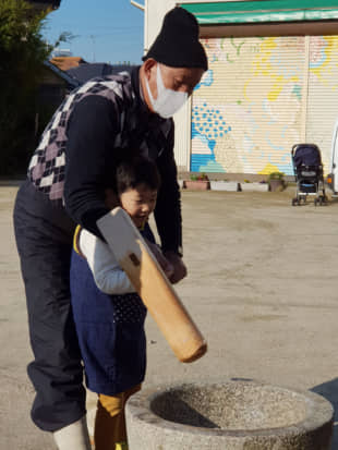 Passing down tradition: Tadashi Amano teaches his 7-year-old grandson, Minato, how to hold a mallet that is used to make rice cakes for the holidays. | AMY CHAVEZ