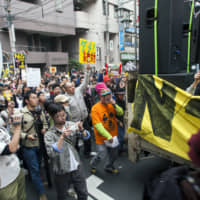 Speak out: Koenji's counter-cultural vibe attracted those tourists and visitors looking for something a little less neon in their Tokyo experience. In this 2011 photo, Rankin' Taxi leads one of the first post-Fukushima antinuclear demonstrations. | JAMES HADFIELD
