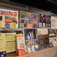 A wall of his own: Flyers promoting various community events line the walls of Sam's Bar TalkEigo in Fukuoka. Owner Sultan 'Sam' Vidhani says the hardest part of starting his business was finding a landlord who would rent to a non-Japanese person. | IRINA GRIGOROVICI