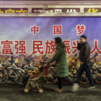 Pedestrians in walk past a government mural referencing the 'Chinese Dream' in the city of Wuhan, Hubei province, on Dec. 9. | BLOOMBERG