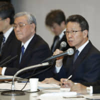 Under fire: Kansai Electric Power Co. President Shigeki Iwane (center) has said he will step down when a third-party panel reports the results of its investigation into the scandal. | KYODO
