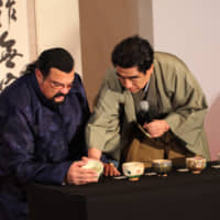 International Sports Promotion Society Chairman Haruhisa Handa teaches actor Steven Seagal how to hold a Japanese teacup at the Hilton Tokyo Odaiba Hotel on Dec. 7. | ISPS