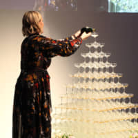 Tindall pours Champagne into an illuminated pyramid of stacked glasses during the talk show. | ISPS