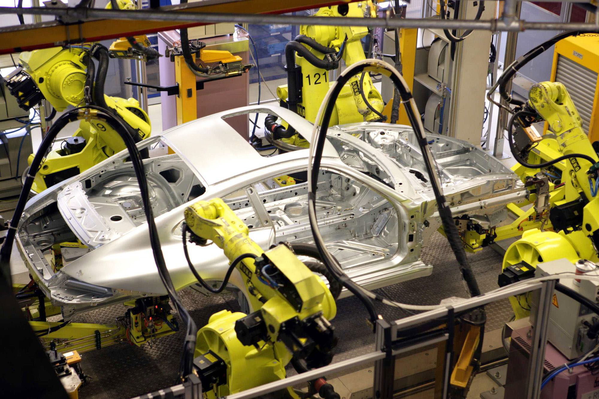 Four robots arms weld a Porsche 911 Coupe sports car body at a factory in Germany. | BLOOMBERG NEWS