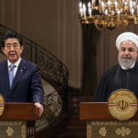 Prime Minister Shinzo Abe and Iranian President Hassan Rouhani (right) hold a joint press conference at the Saadabad Palace in Tehran on June 12. | AFP-JIJI