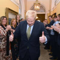 British Prime Minister Boris Johnson is greeted by staff as he arrives back at 10 Downing Street in central London on Friday  following an audience with the queen. | AFP-JIJI