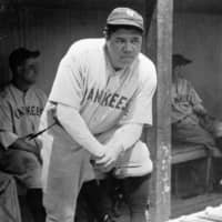New York Yankees slugger Babe Ruth stands in the dugout with a strained muscle in his left leg during a game in Cleveland in 1929. | AP