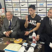 WBA middleweight champion Ryota Murata (center), accompanied by Teiken Promotion President Tsuyoshi Hamada (right) and promoter Bob Arum, answers questions from the media during a news conference after his title bout at Yokohama Arena on Monday. | KAZ NAGATSUKA