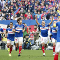 Yokohama F. Marinos players celebrate the team's J. League title-clinching victory over FC Tokyo on Saturday afternoon at Nissan Stadium. | KYODO