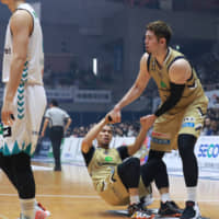 Ryukyu's Yuki Mitsuhara helps teammate Narito Namizato get back up after falling down during Sunday's game against Kyoto in Okinawa City. The Golden Kings defeated the Hannaryz 97-76. | B. LEAGUE