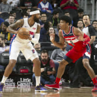 Wizards forward Rui Hachimura (right) guards the Pistons' Markieff Morris during a game on Dec. 16 in Detroit. Hachimura was injured later in the contest. | KYODO
