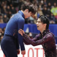 Shoma Uno (left) is congratulated by Yuzuru Hanyu after winning the men's competition of the Japan Championships on Sunday in Tokyo. | KYODO