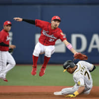 Carp infielder Ryosuke Kikuchi jumps as he attempts to tag the Tigers' Yoshio Itoi during a game on August 9. Kikuchi was unable to land an MLB deal this offseason. | KYODO
